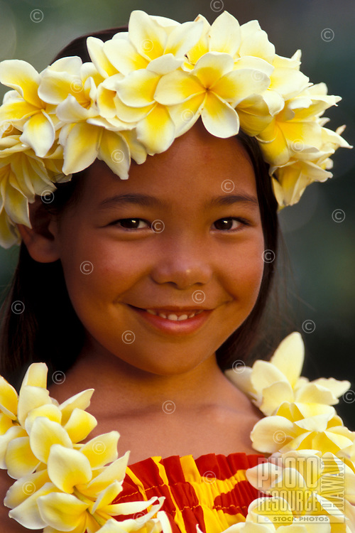 A young local girl wears yellow plumeria flowers with a smile.