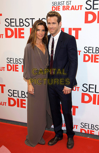 "SANDRA BULLOCK & RYAN REYNOLDS .Premiere of ""The Proposal"", Movie Palace, Munich, Germany..June 29th, 2009.full length brown gold necklace dress blue black suit jacket burgundy maroon tie .CAP/PPG/JH.©Jens Hartmann/People Picture/Capital Pictures"
