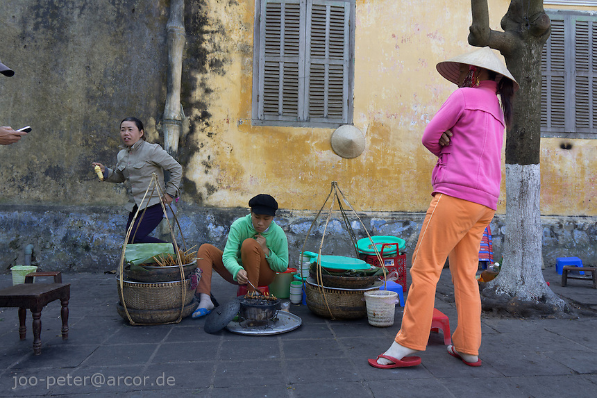street scene with women chatting in the city Hoi An, Vietnam