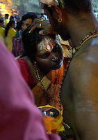woman receiving blessings while  Thaipusam ceremonies,  Batu Caves, Kuala Lumpur, Malaysia, 2012. Thaipusam ceremonies, celebrated by tamile Hindu community in Malaysia, take place  in Sanctuary of Batu Caves at the border of Kuala Lumpur, each year around end of January or beginning of February, according to Hindu moon calendar. The event is paying hommage to Lord Murugan, a spirit or god created by Shiva to lead the army of gods against the army of evil demons, finally defeating the evil spirits. There are many ways to present offerings or sacrifices for this major religious event. Devotees mortify their bodies by carrying heavy kavaris with spears fixed in their skin or fruits, flowers and little post with holy milk fixed with hooks in their skin, ascending the stairways to the sanctuary in trance, `followed by assistant  taking care and musicians playing loud and fast rhythmic trance music.  Many families shave their head in a ritual before ascending the stairways, as part of rituals to obtain salvation for their ancestors.