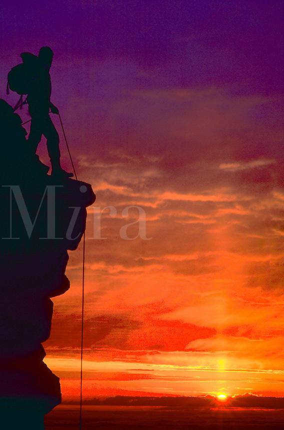 Silhouette of a climber atop Pikes Peak in Colorado against a deep purple and red sunset sky.