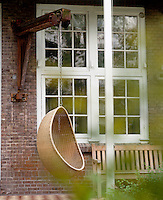 In the garden of an Amsterdam apartment a contemporary hanging chair is suspended from one of the original beams