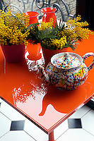 Pots of mimosa and a colourful splatterware teapot make the most of the orange glass-topped table in the breakfast area