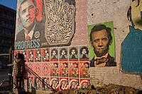 Inauguration-goers stand in front of one of several Obama art installations done by icon artists Shaepard Fairey.  This particular installation can be found near U street, a historically black strip of commercial passing through DC.  Inauguration.  Photographs from around DC including Adam's Morgan, U-Street, and Howard University.  For many, U-Street is regarded as the soul of DC, a traditionally black part of town cutting through the the northern quadrants of the Capital.