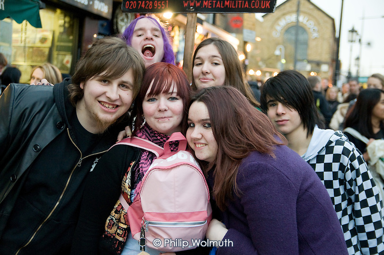 Teenagers in Camden Town, one with a pierced lip and one with a pierced tongue.