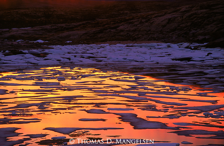 Sunset colors are reflected in the water of Wager Bay, littered by ice from the spring breakup.<br /> Nunavut, Canada