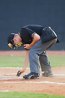 Umpire Charlie Tierney cleans home plate during an Appalachian League game between the Pulaski Mariners and the Bristol White Sox at Boyce Cox Field August 28, 2010, in Bristol, Tennessee.  Photo by Brian Westerholt / Four Seam Images
