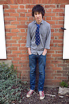 Model released teenage boy portrait standing against a wall, UK