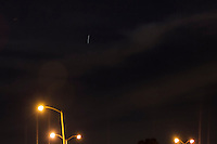 In a five second exposure, the International Space Station, ISS, is seen to draw a clear line in the sky above the parking lot lights along San Francisco Bay.
