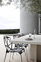 A white concrete table lined with black chairs provides a place for outdoor dining on the poolside terrace