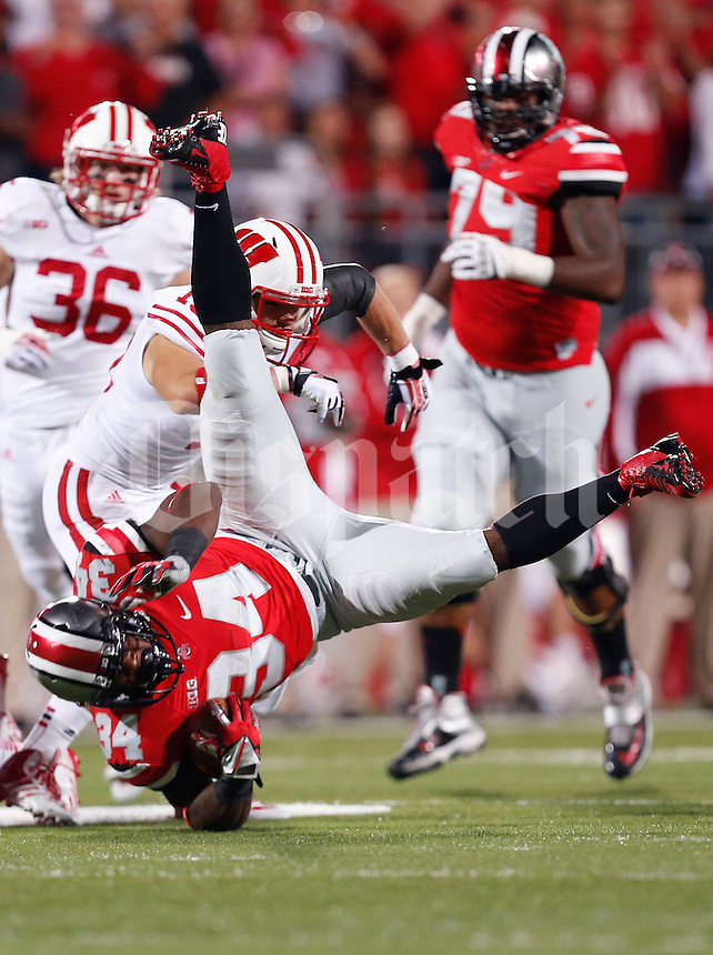 Ohio State Buckeyes running back Carlos Hyde (34) gets flipped Wisconsin Badgers safety Leo Musso (19) in the first quarter of the NCAA football game at Ohio Stadium in Columbus, Saturday evening, September 28, 2013. As of halftime the Ohio State Buckeyes led the Wisconsin Badgers 24 - 14. (Columbus Dispatch  / Eamon Queeney)