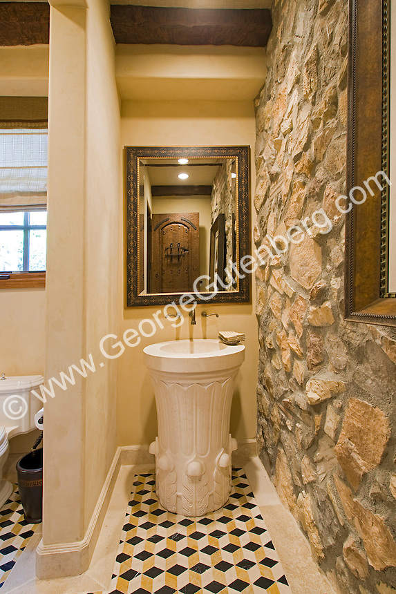 Powder room with white pedestal sink and stone wall Stock photo of residential guest bathroom, powder room.