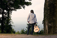 A guitar maker stands with his guitar next to an old cabin high in the North Carolina mountains.