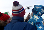 (Boston MA 12/17/17) Families watch as Santa arrives by an executive helicopter from the North Pole to Boston's North End, Sunday, December 17, 2017, at Puopolo Park in Boston. After meeting with some children Santa was whisked off in an old fire truck to the Steriti Staking Rink for holiday music and caroling, face painting and refreshments. The event was sponsored by a number of North End businesses and organizations. Herald Photo by Jim Michaud