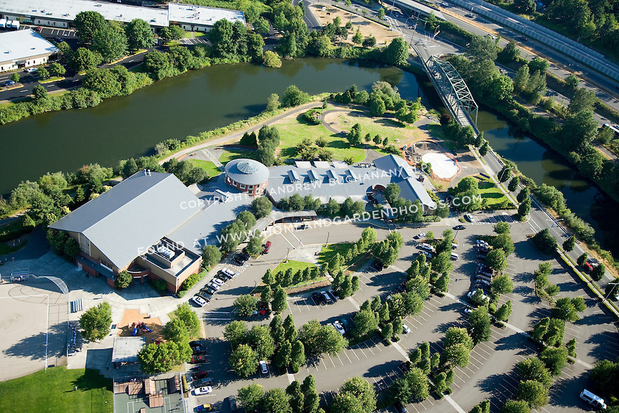 A sunny, summer afternoon aerial photo of the Tukwila Community Center in Tukwila, WA just south of Seattle.  Because of its waterfront location on the Green River, the parking lot of the newly re-designed center includes bioswales to capture, filter, and mitigate storm water runoff.