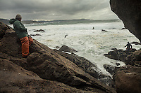 """December 16, 2011 - Laxe (La Coruña). """"Feuto"""" - a retired percebeiros - observes his son finding his way on the cliff. He can't stay home when the sea is in bad conditions and he stays all the time with his son. © Thomas Cristofoletti 2011"""