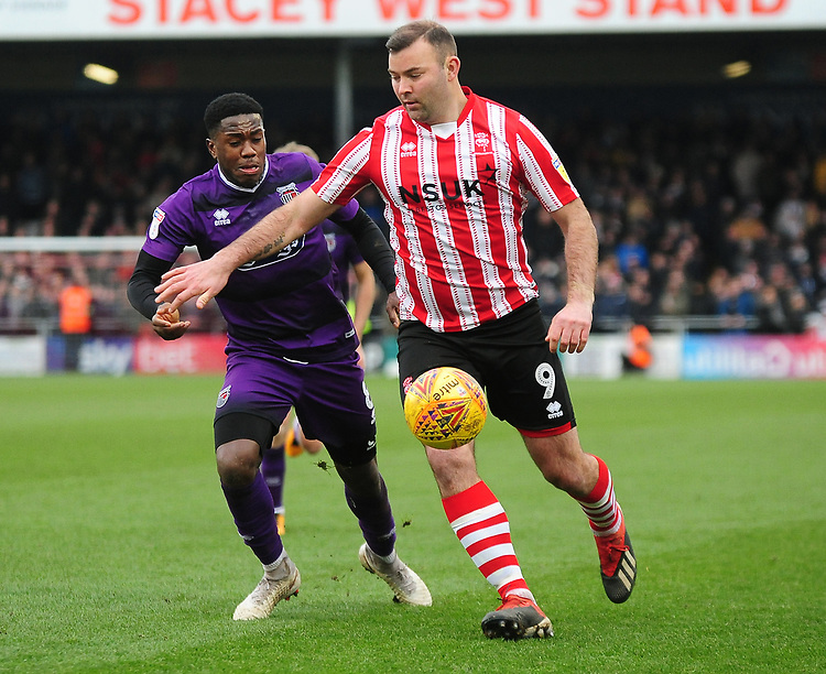 Lincoln City's Matt Rhead under pressure from Grimsby Town's Mitch Rose<br /> <br /> Photographer Andrew Vaughan/CameraSport<br /> <br /> The EFL Sky Bet League Two - Lincoln City v Grimsby Town - Saturday 19 January 2019 - Sincil Bank - Lincoln<br /> <br /> World Copyright &copy; 2019 CameraSport. All rights reserved. 43 Linden Ave. Countesthorpe. Leicester. England. LE8 5PG - Tel: +44 (0) 116 277 4147 - admin@camerasport.com - www.camerasport.com