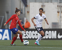 Korea Republic forward Jeoun Eunha (18) dribbles as USWNT midfielder Carli Lloyd (10) defends. In an international friendly, the U.S. Women's National Team (USWNT) (white/blue) defeated Korea Republic (South Korea) (red/blue), 4-1, at Gillette Stadium on June 15, 2013.