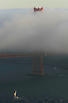 The San Francisco fog creeps over the deck of the Golden Gate Bridge as a boat sails out at dusk in California.