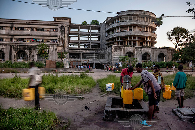 People fill vessels with water from a stand pipe, the only one available for about six thousand squatters living in the shell of the former Grand Hotel building. Once a luxury destination for the wealthy and the continent's biggest hotel, the building is now a concrete shell. Those unable to occupy one of the rooms sleep in the corridors, basements and even on the roof of the building.