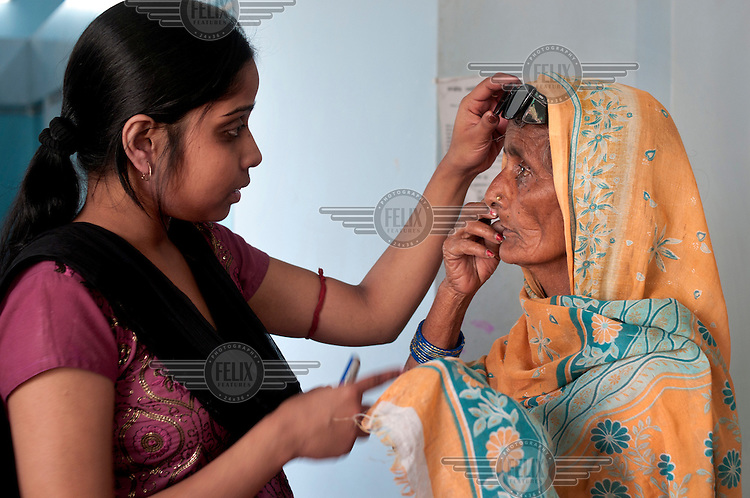 A cataract patient comes back two weeks after her operation to have her eyes checked - here she's with opthalmic assistant at the Akhand Jyoti Eye Hospital.