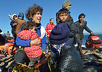 A foreign volunteer hugs a refugee child shortly after she and her family arrived on a beach near Molyvos, on the Greek island of Lesbos, on November 2, 2015, after crossing the Aegean Sea from Turkey. Local and international volunteers welcomed the arriving refugees with food and medical care and dry clothes before the newcomers proceeded on their way toward western Europe. Their boat to Greece was provided by Turkish traffickers to whom the refugees paid huge sums to arrive in Greece.