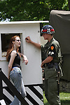 A military MP soldier at a gate flirting with a young girl