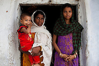 Sadma Khan (in purple), 19, poses for a portrait with her child and mother (in orange) at the door of her shared house in her mother's extended family's compound in a slum area of Tonk, Rajasthan, India, on 19th June 2012. She was married at 17 years old to Waseem Khan, also underaged at the time of their wedding. The couple have an 18 month old baby (in red) and Sadma is now 3 months pregnant with her 2nd child and plans to use contraceptives after this pregnancy. She lives with her mother since Waseem works in another district and she can't take care of her children on her own. Photo by Suzanne Lee for Save The Children UK