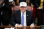 United States President Donald J. Trump tries on a hat as he welcomes the 2019 NCAA Division I Women's Basketball National Champions, the Baylor Lady Bears, in the Oval Office of the White House on April 29, 2019 in Washington, DC. <br /> Credit: Oliver Contreras / Pool via CNP