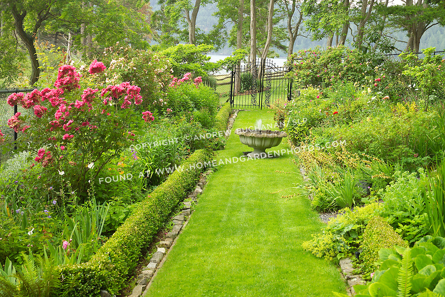 With the ocean in the background, a grass path leads through lush planting beds in this Pacific Northwest garden.