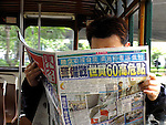 Man reading a chinese newspaper in a tram.