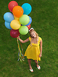 Young smiling woman standing on grass with a bunch of colorful air balloons in her hand.