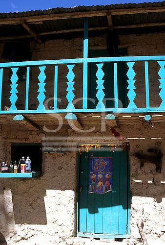 Inca Trail, Peru. Small shop at Llactapata with green door and balcony and adobe walls.