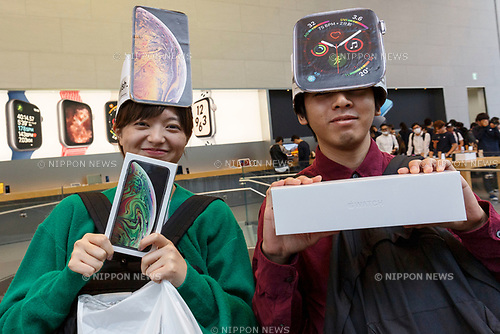Apple fans pose for a photograph after buying a new iPhone XS Max and iWatch Series 4 at the Apple Store in Omotesando on September 21, 2018, Tokyo, Japan. Apple fans lined up patiently in the early morning rain to get the new iPhone models (XS and XS Max) and the new iWatch (Series 4). The new iPhone XS costs JPY 112,800 for the 64 GB model, the iPhone XS Max costs JPY 124,800 JPY for the 64 GB model, and iWatch Series 4 costs JPY 45,800. (Photo by Rodrigo Reyes Marin/AFLO)