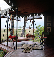 The swing bed is the most comfortable and hotly contested seat in the camp and hangs beyond the library tent with a view over the salt pans
