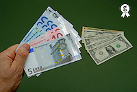 Man holding Euro banknotes, close-up of hand, US dollars in background (Licence this image exclusively with Getty: http://www.gettyimages.com/detail/sb10064360b-001 )