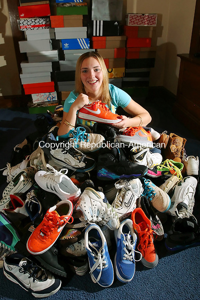 WATERBURY, CT 01/07/08-010708BZ06- Kennedy High School junior Amber Alberto poses in the living room of her Waterbury home with some of her basketball sneakers. She estimated she had 87 pair in the photo but said she had more in her closet.   <br /> Jamison C. Bazinet Republican-American