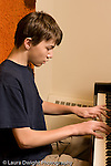 Middle School grade 8 music education boy playing piano in lesson vertical