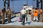 "Roger Meekins, 80, boards the ferry ""Neuse"" on Monday, Aug. 29, 2011, in Rodanthe, NC.  Meekins was barefooted, carrying only a briefcase full of medications and his wife's jewelry.  He and his wife Celia Meekins were leaving Rodanthe for the mainland in Stumpy Point, NC, after surviving Hurricane Irene and a fire that destroyed their Rodanthe home, and all of Roger's shoes, the day before.  Photo by Ted Richardson"