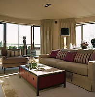 The contemporary living room is decorated in a neutral palette with accents of red in the cushions and coffee table