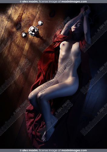 Beautiful naked woman in red kimono with tied hands lying on the floor in dim dramatic light view from above