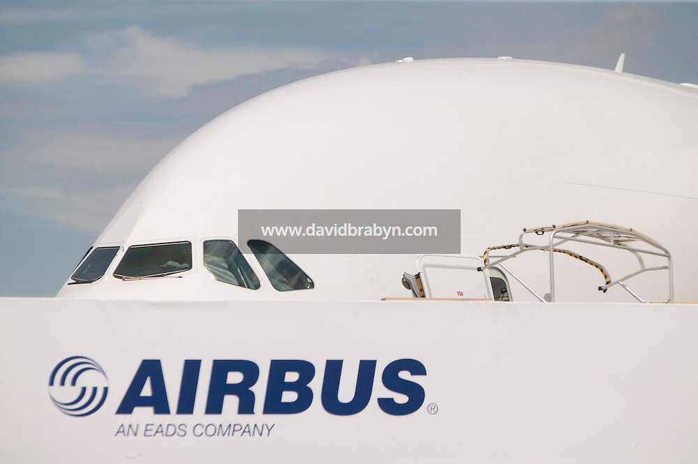 An Airbus A380 standing on display peers above an Airbus sign at the Le Bourget airfield near Paris, France during the International Paris Air Show, 18 June 2007.