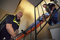 Switzerland. Canton Ticino. Bioggio. A senior woman lying down on an emergency medical stretcher is carried down the stairs by a paramedics team. The elderly woman is suffering from drug poisoning for taking by mistake an overdose of prescribed drugs. The paramedics wear blue uniforms and work for the Croce Verde Lugano. The man (R) is a professional certified nurse, the other man (L) is a volunteer specifically trained in emergency rescue. The Croce Verde Lugano is a private organization which ensure health safety by addressing different emergencies services and rescue services. Volunteering is generally considered an altruistic activity where an individual provides services for no financial or social gain to benefit another person, group or organization. Volunteering is also renowned for skill development and is often intended to promote goodness or to improve human quality of life. 14.01.2018 © 2018 Didier Ruef