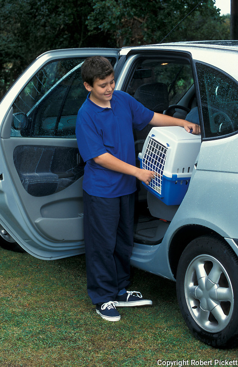 Young Boy with pet cat in carry travel box, putting it in car for trip to vets, aged 11 years old, case