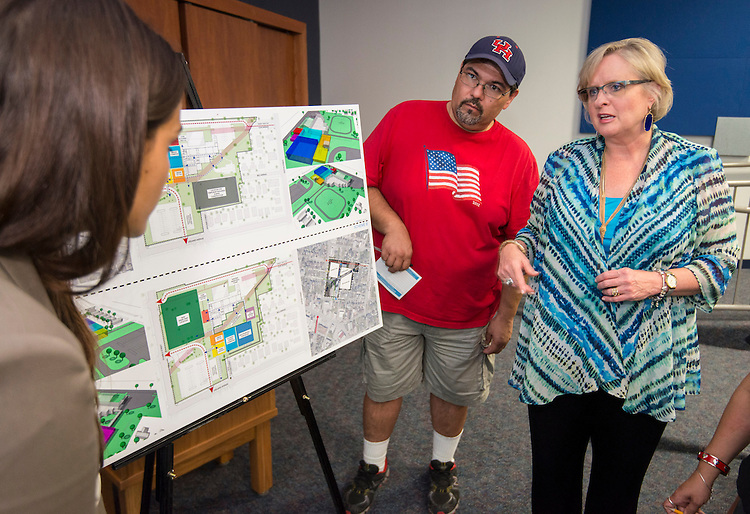 Eastwood Academy High School principal Paula Fendley, right, discusses proposals from ProZign architects during a community meeting, June 19, 2014.