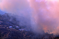 870000399 a los angeles county fire fighting helicopter buried deep in thick smoke flies over homes on a burning hillside in the path of the topanga fire in the hills above the san fernando valley in southern california