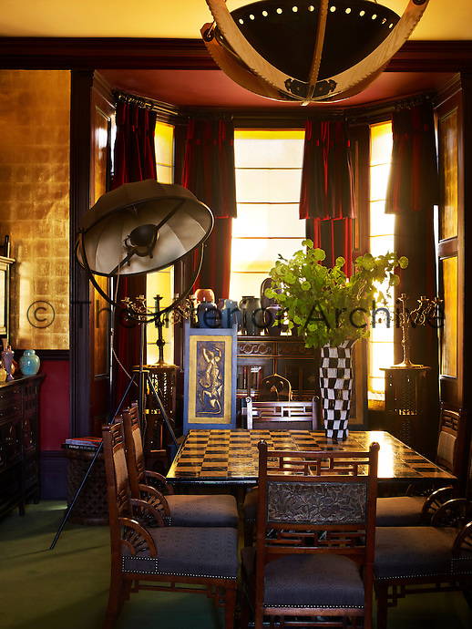 The gilded walls of the dining room cast a warm glow over the chessboard dining table which is surrounded by Arts & Crafts chairs