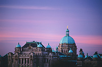 Glowing cupolas and statute on Parliament Buildings (F.M Rattenbury architect) in Victoria, BC during sunset in winter.