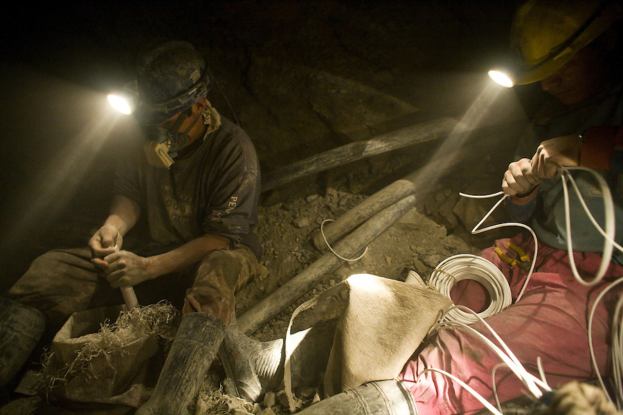 Miners packing ammonium nitrate and preparing blasting caps in La Negra mine.