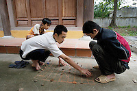 "Vietnam. Ha Tay province. Lai Xa. On a rainy sunday afternoon, two young men kneel down and play a board game drawn with chalk on the ground. A board game, which is a game in which pieces are placed on, removed from, or moved across a ""board"" (a premarked surface usually specific to that game). Lai Xa is a typical hamlet (village) and is part of the Kim Chung commune located 15 km west of Hanoi. 05.04.09 © 2009 Didier Ruef"